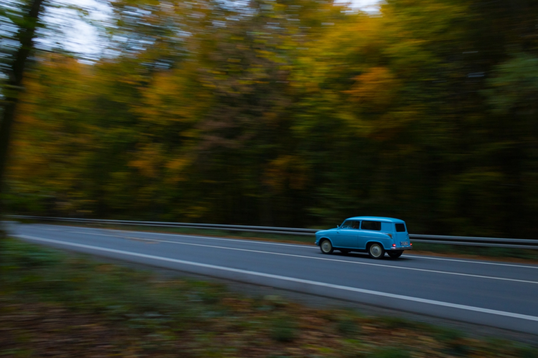 Foto: Blauer Oldtimer fährt auf der Landstraße
